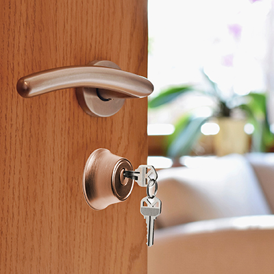 Image of keys in open apartment door.