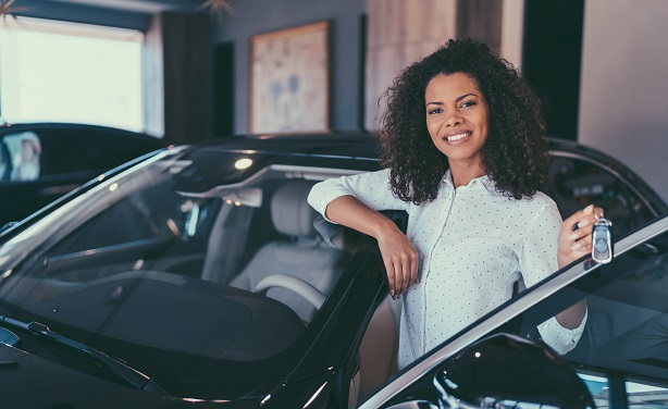 Woman standing next to new car holding up keys